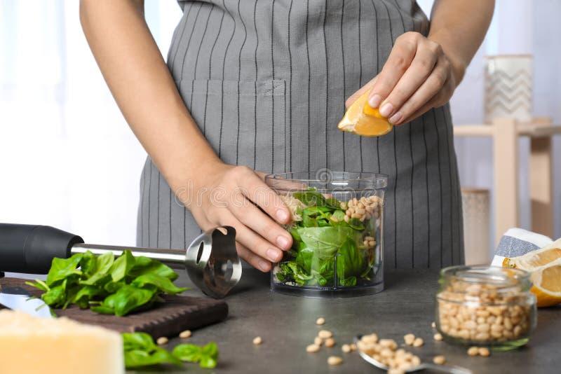 Woman making basil pesto sauce stock image