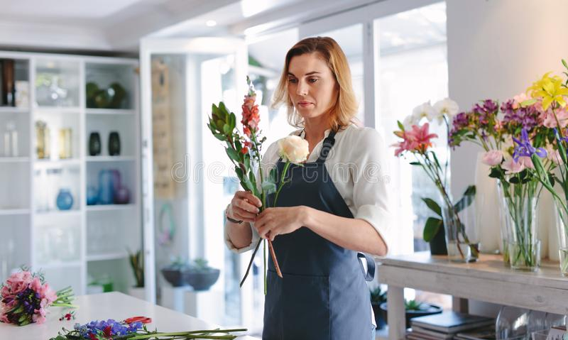 Woman making a bouquet with fresh flowers stock photography