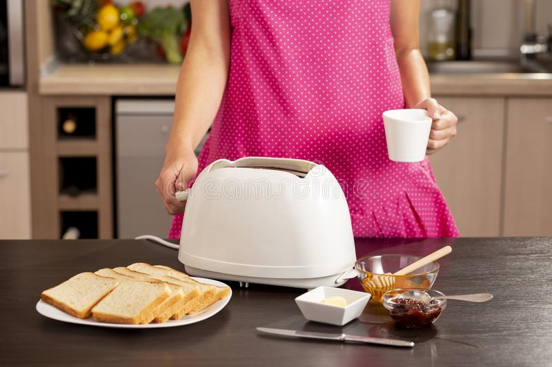Woman making breakfast and drinking coffee royalty free stock photography