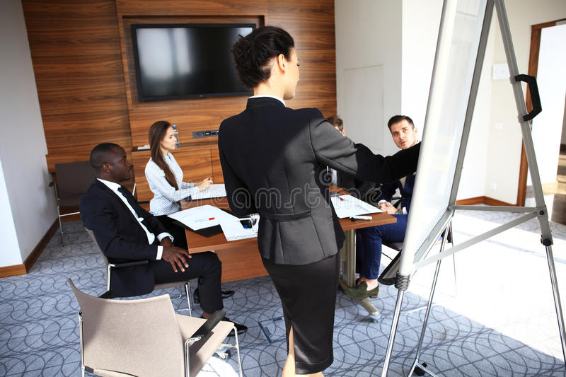 Woman making business presentation to a group royalty free stock photo