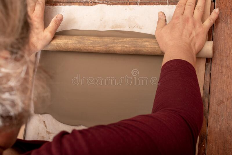 Woman making ceramic and pottery tableware at the workshop, working with clay. Close up stock photo