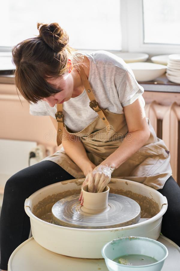 Woman making ceramic pottery on wheel, hands close-up. Concept for working woman in freelance, business, hobby stock photo