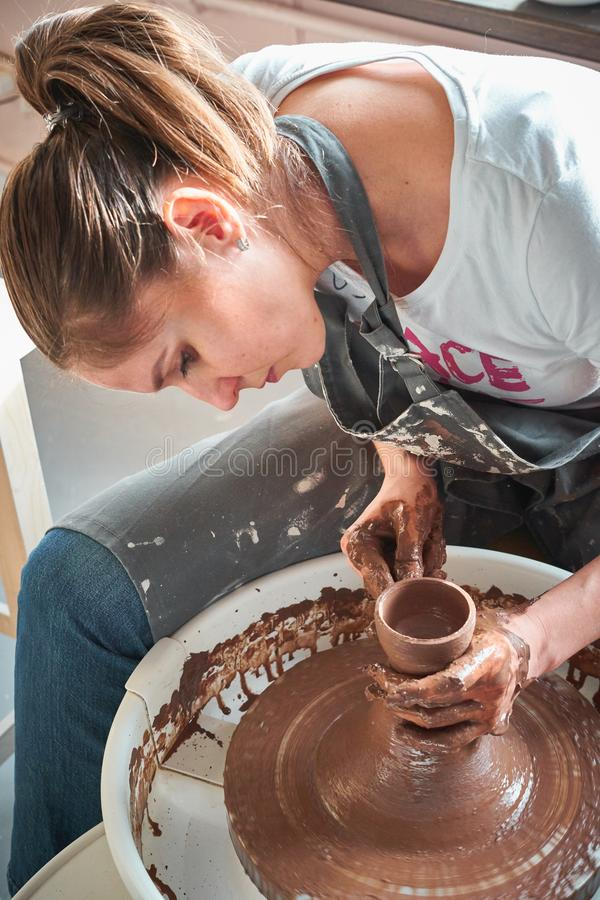Woman making ceramic pottery on wheel, hands closeup. Concept for woman in freelance, business, hobby royalty free stock image