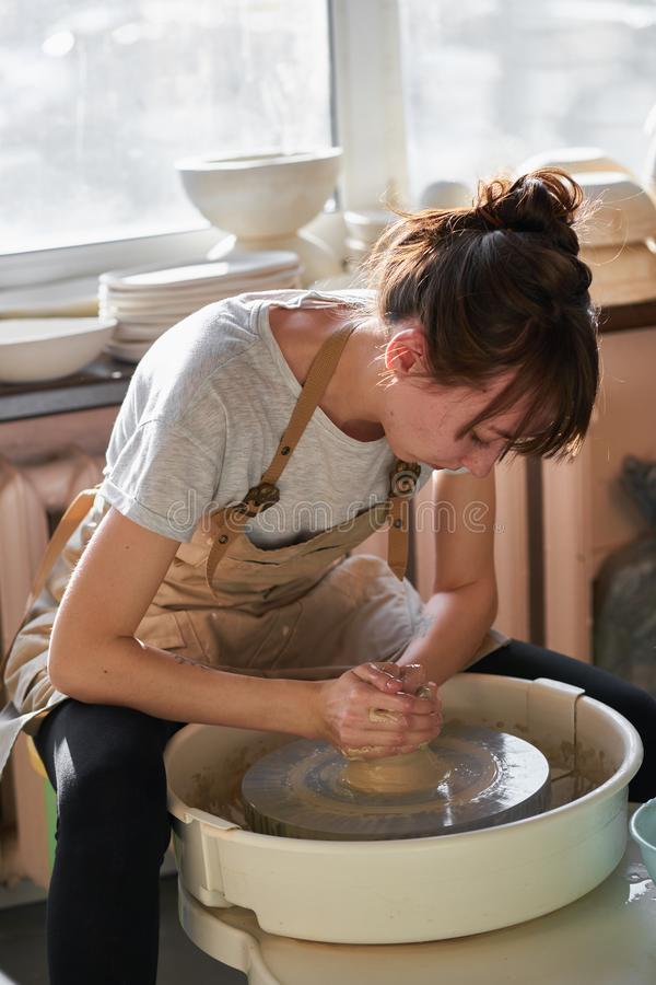 Woman making ceramic pottery on wheel, sun light. Concept for working woman in freelance, business, hobby stock photos