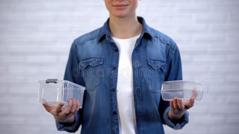 Woman making choice between bioplastic food container and non-disposable box. Stock photo stock image