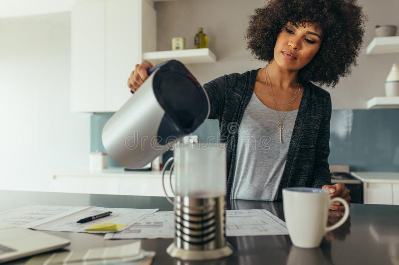 Woman making coffee at home office stock images