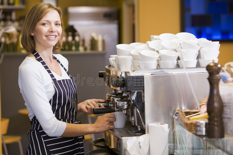 Woman making coffee in restaurant smiling.  royalty free stock images