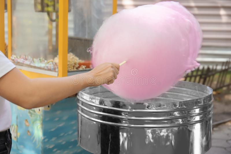Woman making cotton candy in floss machine royalty free stock photos
