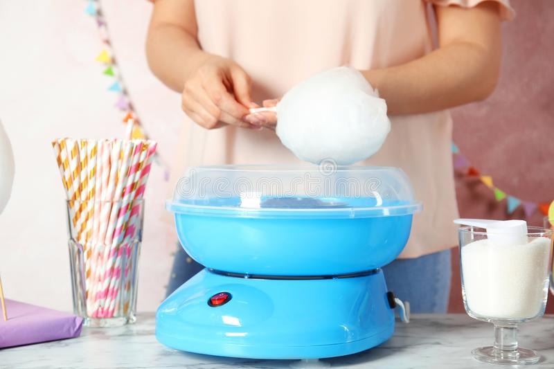 Woman making cotton candy using modern machine at table stock photo