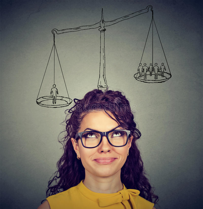 Woman making a decision with scale above head and people on a balance. Smart woman making a decision with scale above head and people on a balance royalty free stock images