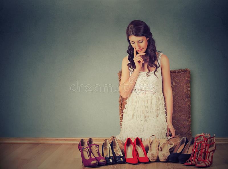 Woman making decisions picking right pair of high heel shoes stock image