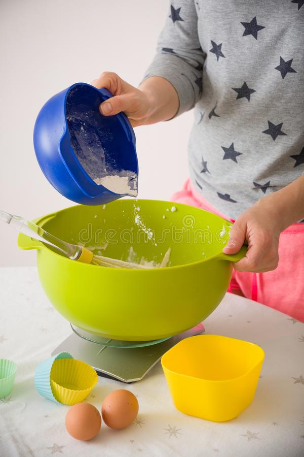 Woman making dough for muffins. Mixing flour, sugar, eggs and other ingredients from colorful bowls. Homemade food, baking at home stock image