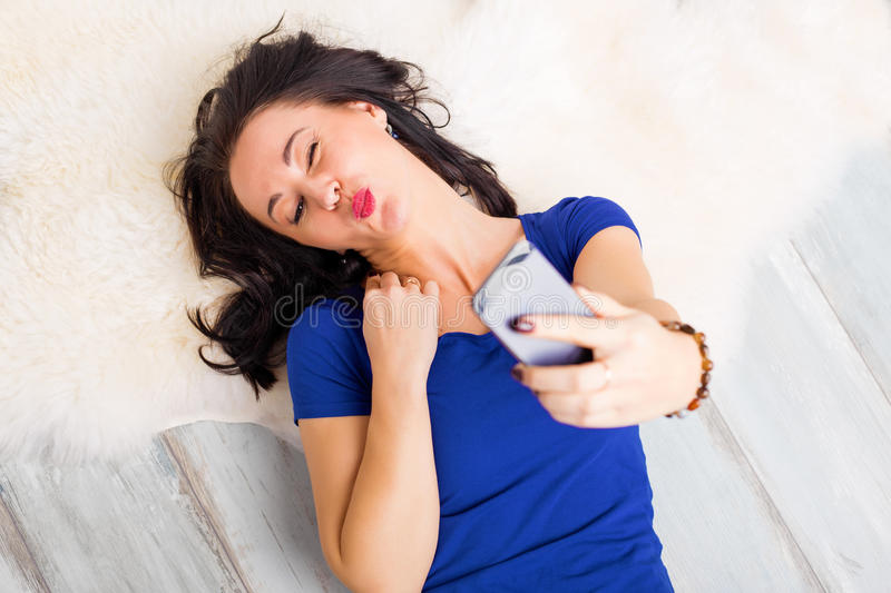 Woman making a duckface and taking a selfie royalty free stock photography