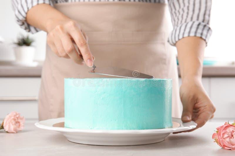 Woman making fresh delicious birthday cake in kitchen royalty free stock photos