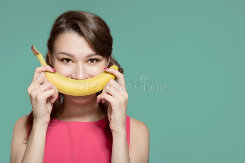 Woman making fun of banana. Turquoise background stock photography