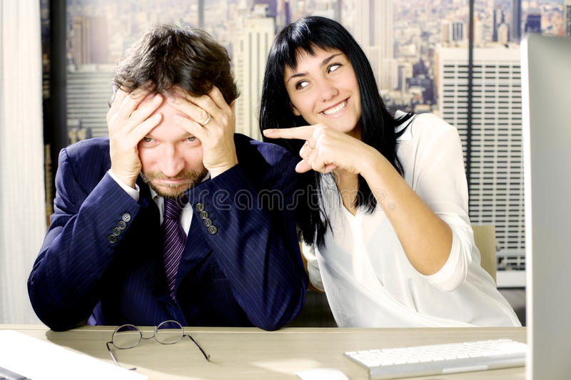 Woman making fun of sad business man royalty free stock photo