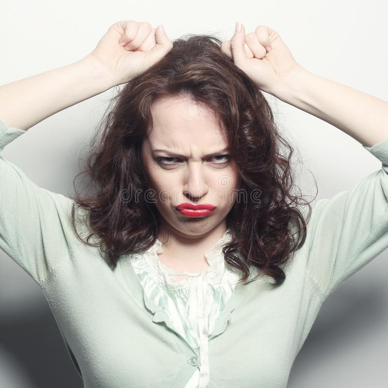 Woman making a funny face. Studio shot royalty free stock image