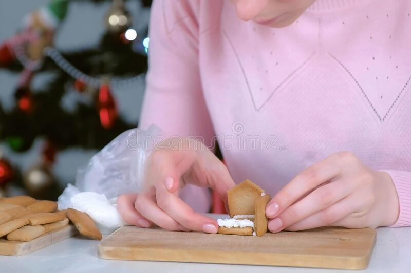 Woman is making gingerbread house connecting details with sugar sweet icing. stock images