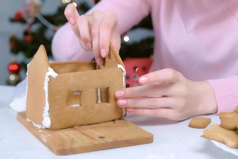 Woman making gingerbread house glues details sugar sweet icing, hands closeup. royalty free stock images