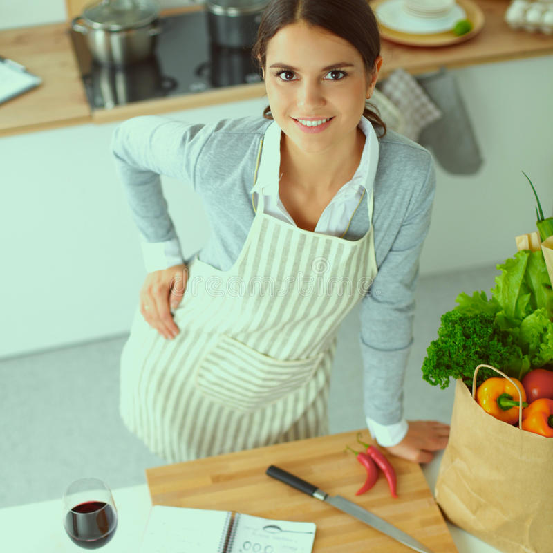 Woman making healthy food standing smiling in kitchen. Woman making healthy food standing happy smiling in kitchen stock photos