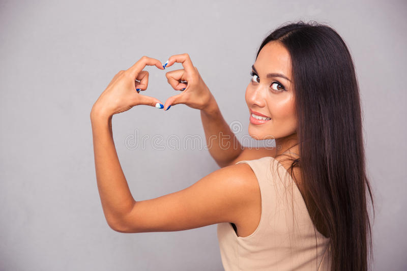 Woman making heart gesture with fingers. Portrait of a happy woman making heart gesture with fingers and looking at camera stock photos