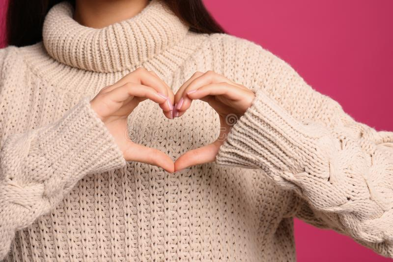 Woman making heart with her hands on color background stock photo