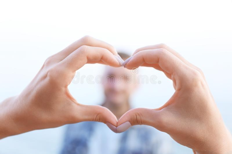 Woman making heart-shaped frame with her hands for young man royalty free stock images
