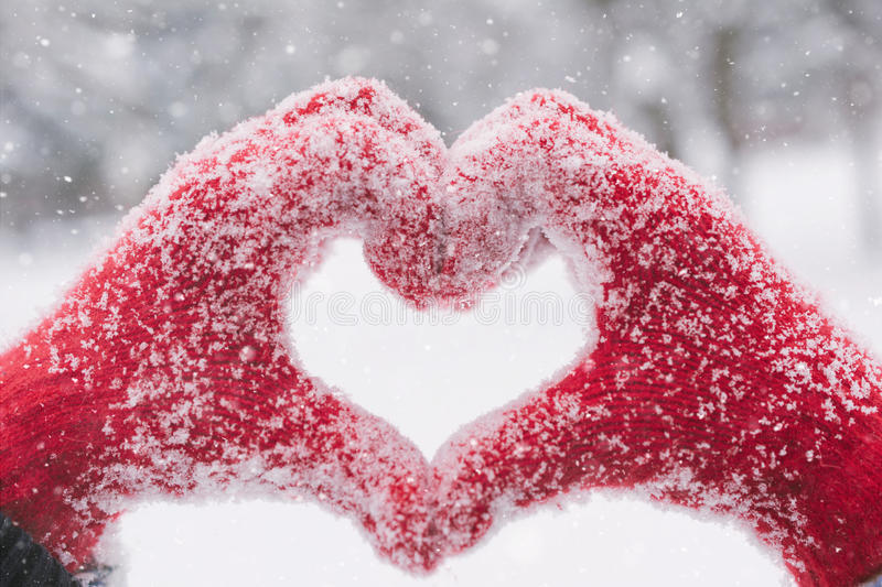 Woman making heart symbol with snowy hands. With snow falling stock photo