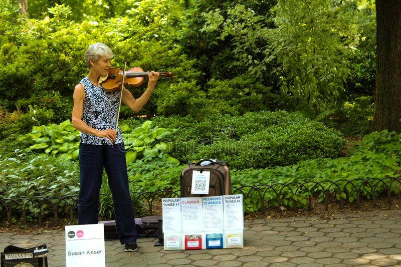 Woman making music in central park stock photo