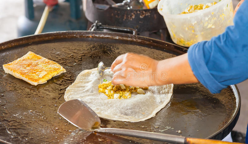 A woman making  Muslim food called Mataba