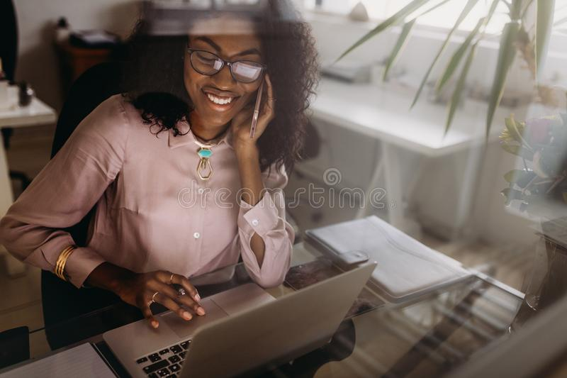 Woman making notes working on laptop at home stock photography