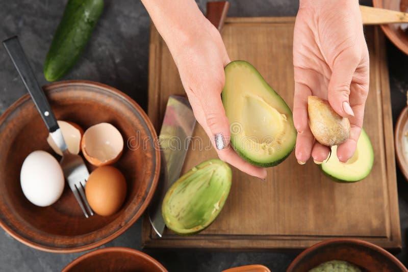 Woman making nourishing mask with avocado stock photography