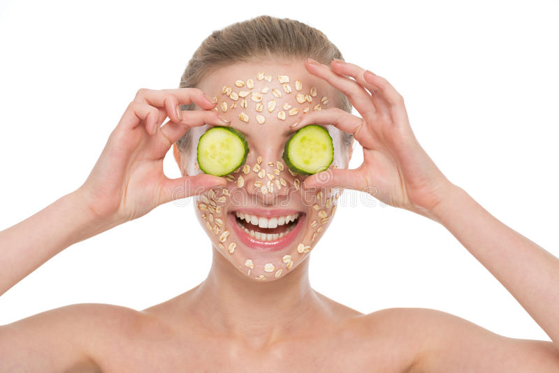 Woman with making oatmeal mask with cucumber stock photography