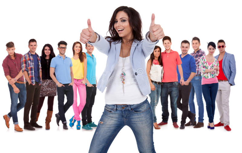 Woman making the ok sign in fron of a grouppeople. Casual young women making the thumbs up ok sign in fron of a group of young people smiling royalty free stock photos
