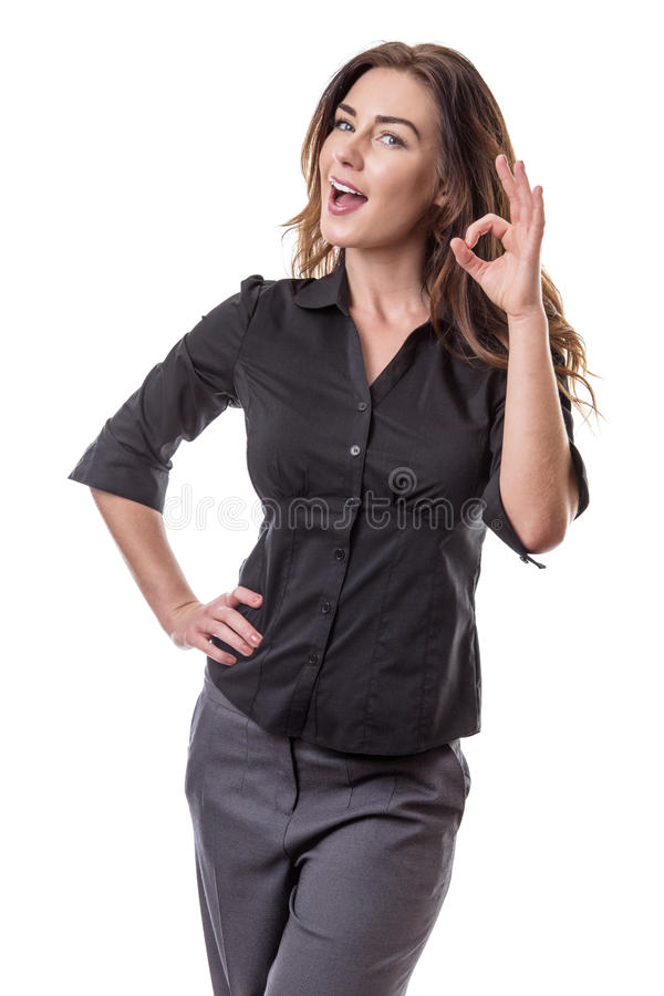 Woman making Ok sign. Pretty young woman making Ok sign with her left hand, whilst her right hand is on her hip. Isolated on white background royalty free stock images