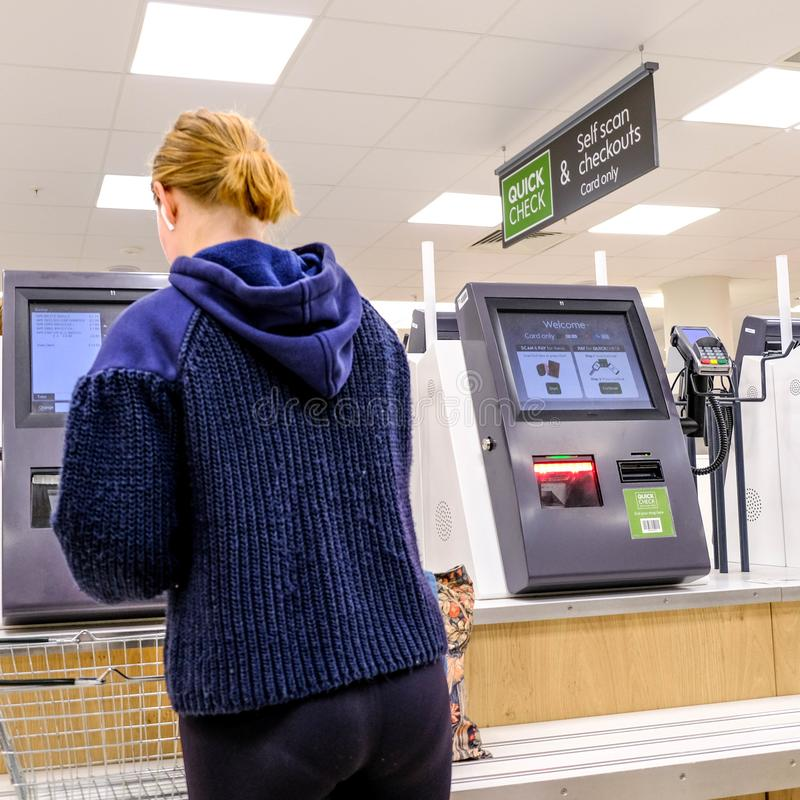 Woman Making Payment At An Automatic Check Out in Waitrose Supermarket royalty free stock image