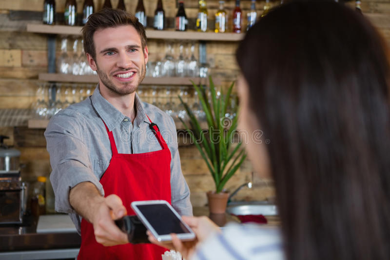 Woman making payment through NFC technology on mobile phone stock image