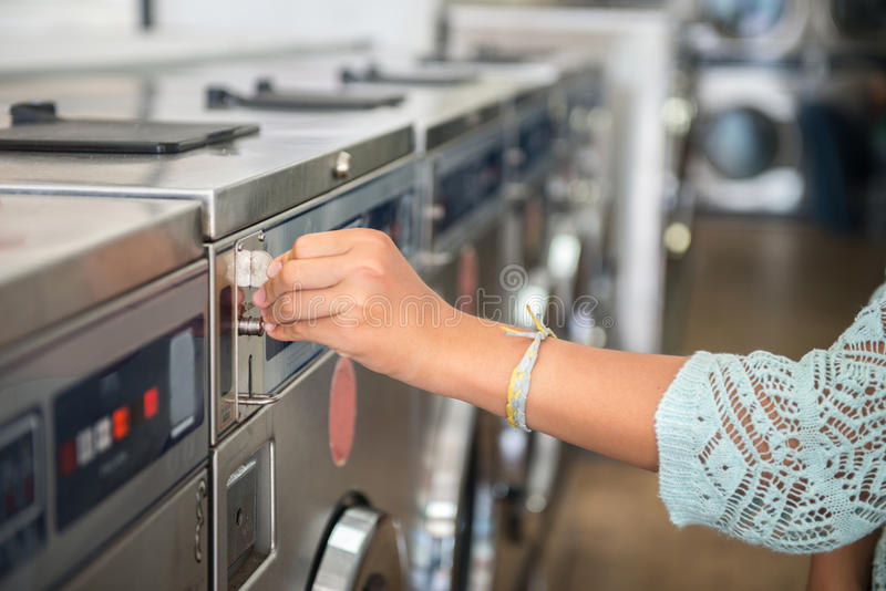 Woman making payment putting quarter to washing laundromat machine in public laundry stock photography