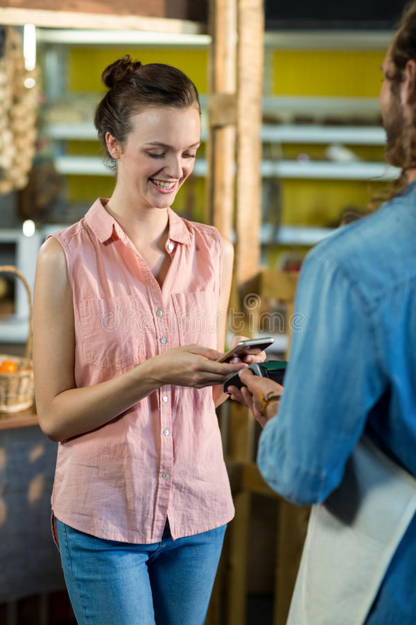 Woman making a payment by using NFC technology royalty free stock photography