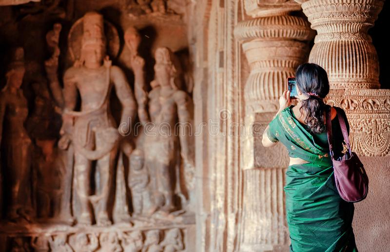 Woman making picture by iphone inside the 6th century Hindu temple with caves. Carvings in ancient places, India.  royalty free stock image