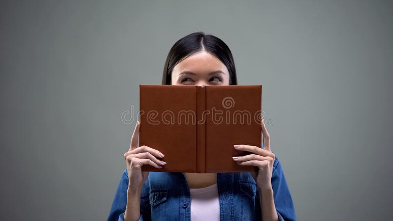Woman making plans and thinking over business strategy hiding behind notebook. Stock photo stock images