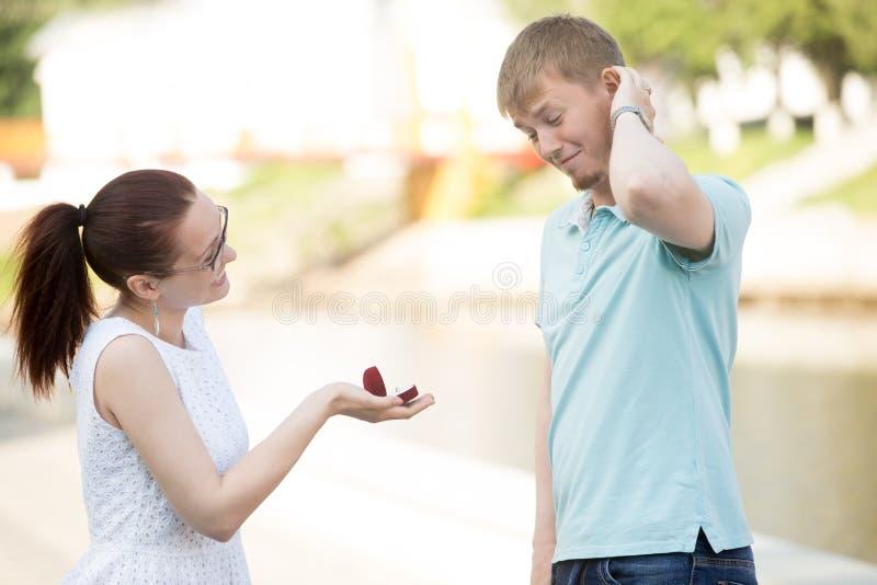 A woman making proposal to boyfriend stock images
