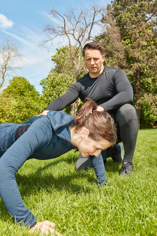 Woman making push ups with Personal Trainer. At the park stock images