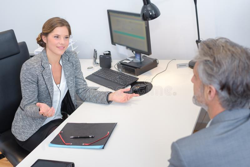 Woman making questioning hand gesture to man stock images