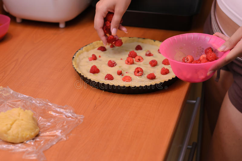 Woman making raspberry cake. royalty free stock photo