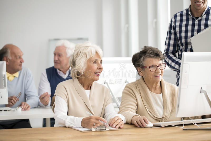 Woman making report. Elder women making report of her friend`s work on computer royalty free stock photos