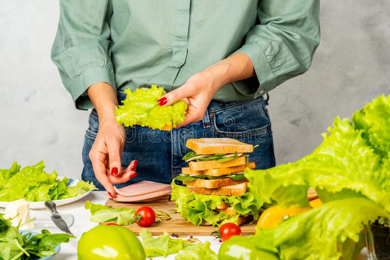 Woman is making sandwiches with ham, butter, lettuce and spinach.  royalty free stock photography