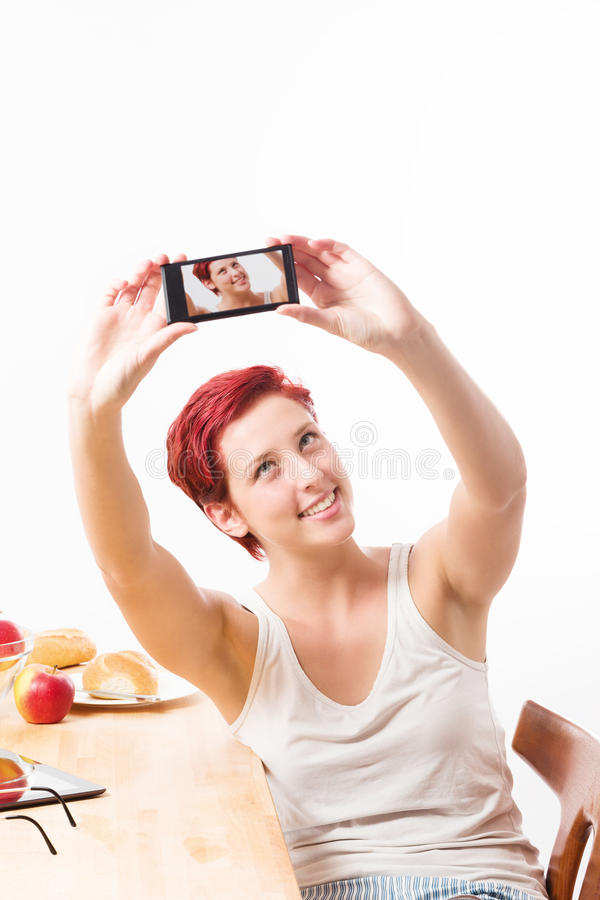 Woman making a self portrait with her smartphone royalty free stock images