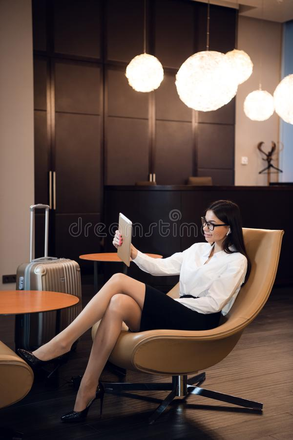 Woman making selfie by tablet in airport waiting room business lounge. Concept of modern technology, communication and stock photo