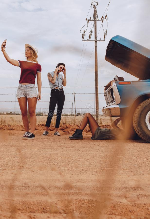 Women on roadtrip having a problem with car royalty free stock photos